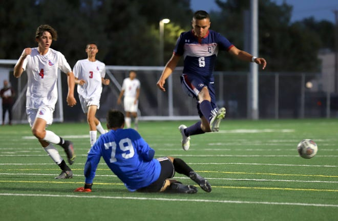 Wildcat junior Abraham Chavez (6) hurdles the Las Cruces goalkeeper in pursuit of a free ball during Wednesday's 3-1 Deming High victory over the Bulldawgs.