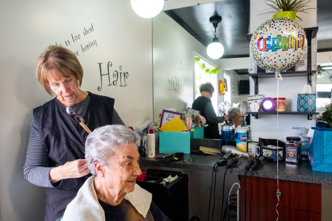 Susan Carrier gives Dovis Lloyd a style Thursday, Sept. 9, 2021, at Shear Style in Marine City. After more than 50 years as a hair dresser, Carrier is retiring.