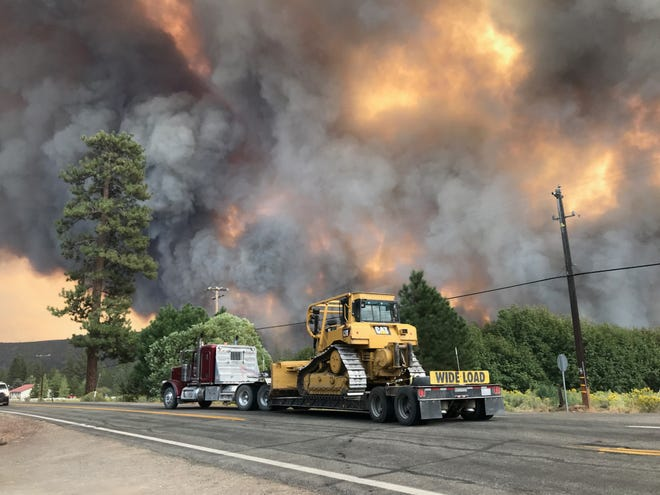 A truck moves a bulldozer to another location in Old Station on Thursday, Sept. 9, 2021 as smoke from the Dixie Fire rises in the background. The fire's proximity prompted authorities to order residents to evacuate on Wednesday night.