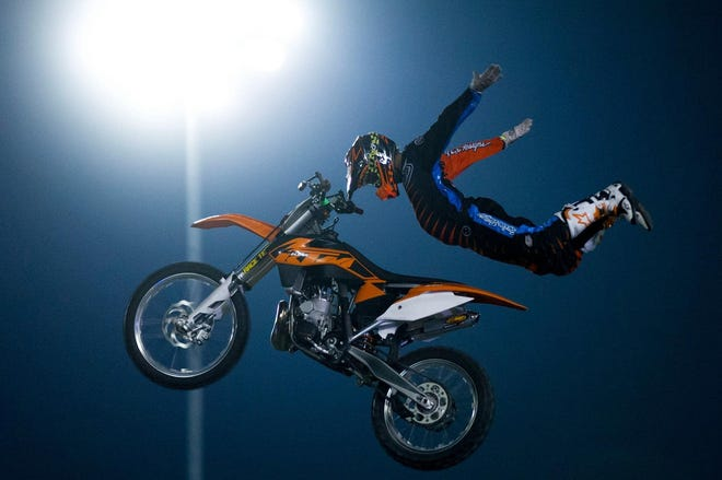 A motocross rider performs a stunt during a Moto Xtreme Circus show.