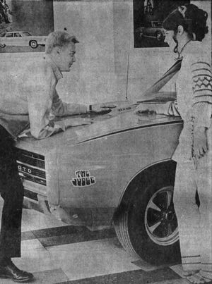 Salesman Rick Geppert explains to Kathy Kindler some of the new features of Pontiac's GTO Judge in 1969.