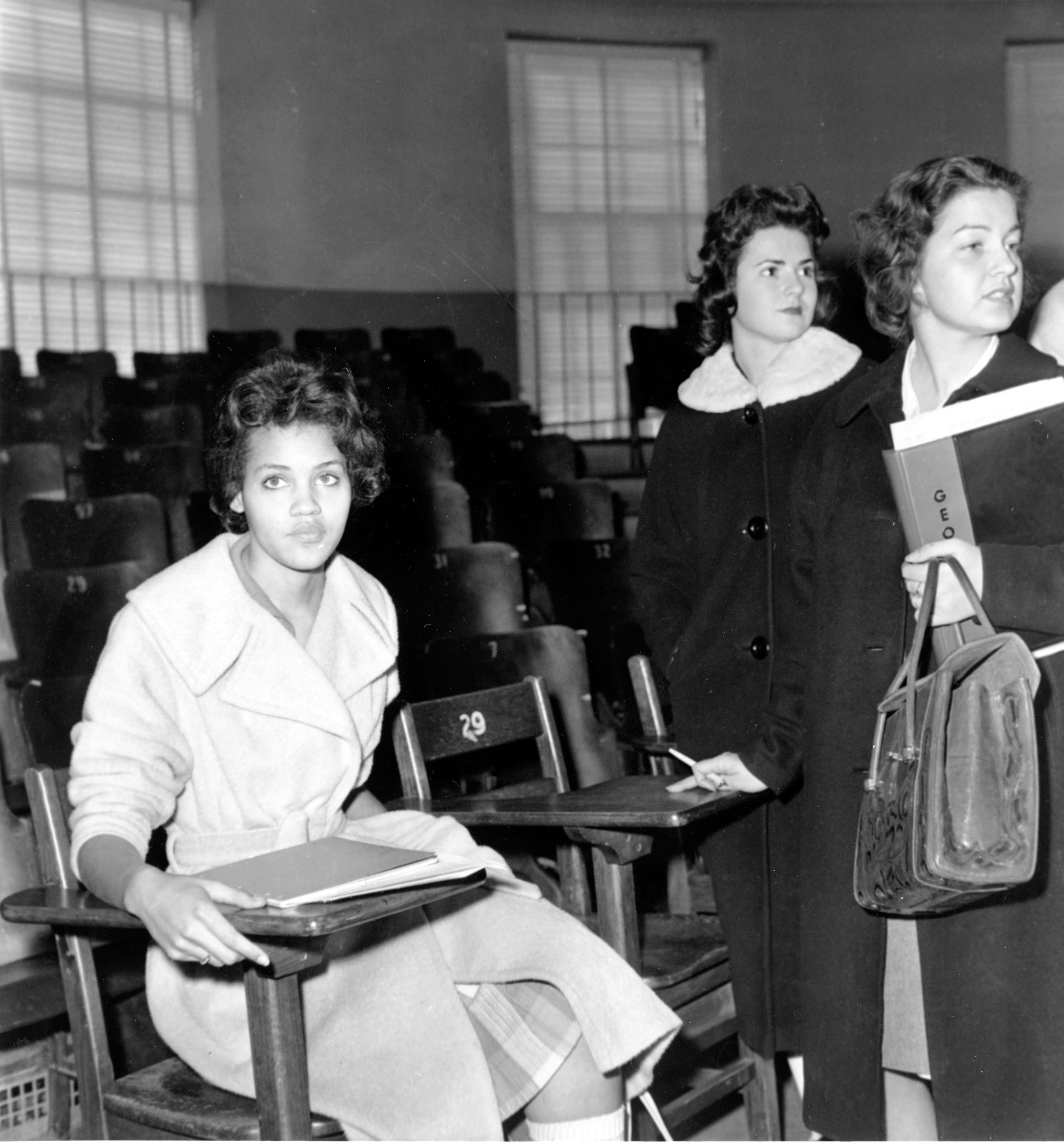 Charlayne Hunter, 18, the first black woman to attend University of Georgia, sits in one of her classes in Athens, Ga., on Jan. 11, 1961. The students at right are unidentified.  Hunter and 19-year-old Hamilton Holmes began classes today under court order.