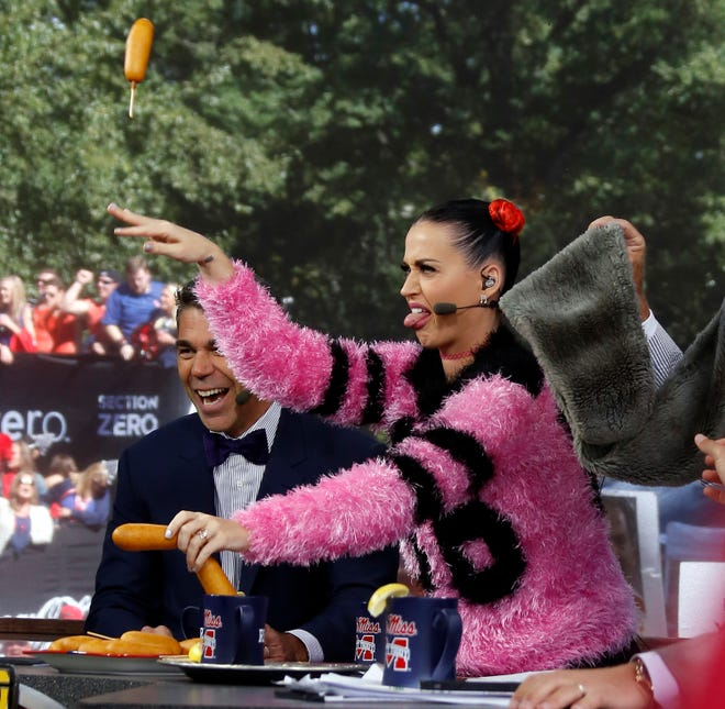 """Singer Katy Perry tosses corn dogs as she shows her displeasure of Alabama being chosen as the favorite over Ole Miss during a telecast of ESPN's """"College GameDay"""" in The Grove at the University of Mississippi on Oct. 4, 2014."""