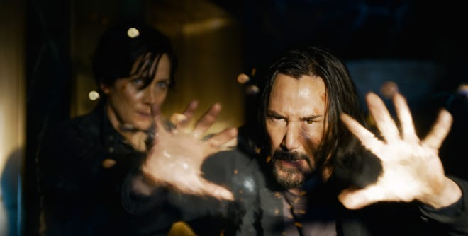 """Neo (Keanu Reeves) and Trinity (Carrie-Anne Moss) reunite in """"The Matrix Resurrections,"""" the fourth movie in """"The Matrix"""" series."""