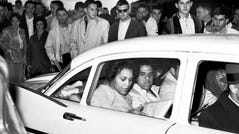 University of Georgia students shout and jeer in this 1961 photo at Charlayne Hunter, 18, left, and Hamilton Holmes, 19, as they leave the administration building after completing registration at Athens, Ga. Admitted under federal court order, they will become the first black students to attend the university in its 175-year history.
