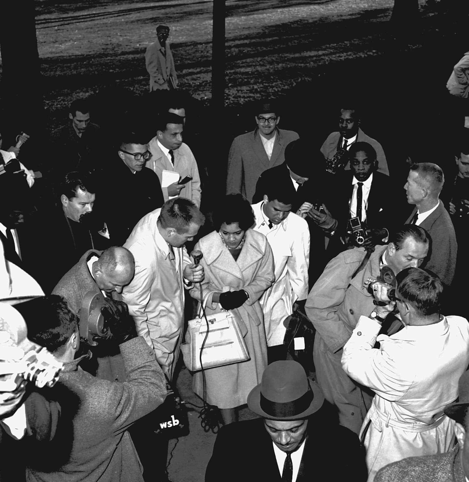 Charlayne Hunter, 18, and Hamilton Holmes, 19, center, have both been admitted to the University of Georgia under federal court order, are surrounded by newsmen as they arrive on the university campus in Athens, Ga., on Jan. 9, 1961.