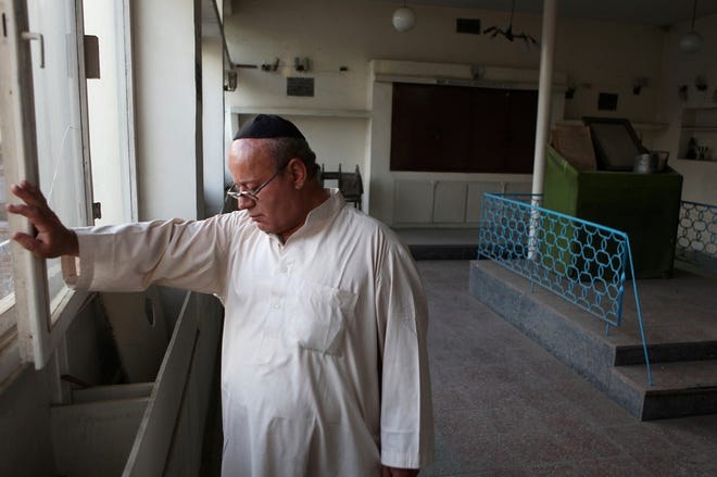 In this Aug. 29, 2009 file photo, Zebulon Simentov, the last known Jew living in Afghanistan, closes the window to the synagogue he cares for in his Kabul home. Simentov who prayed in Hebrew, endured decades of war as the country's centuries-old Jewish community rapidly dwindled has left the country. The Taliban takeover in August, 2021, seems to have been the last straw.
