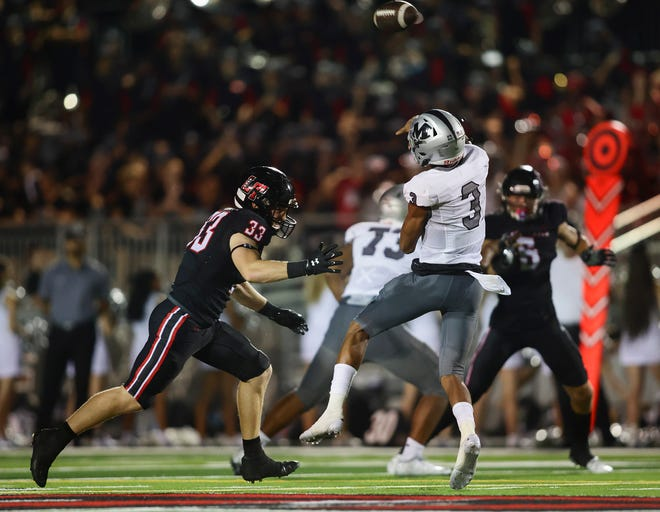 Lake Travis defensive end Max Linhoff, left, puts pressure on Arlington Martin quarterback Cydd Ford in the Cavs' 40-28 win in the season-opener. The Cavs face a third consecutive ranked opponent Friday at Rockwall.