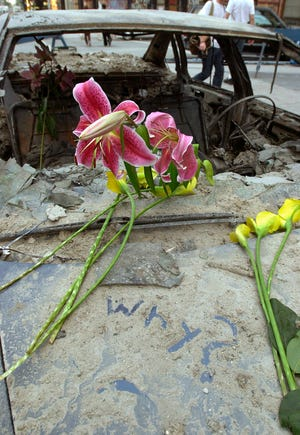 """Flowers sit on the hood of a burned out vehicle on a side street near Ground Zero in New York City. Someone wrote """"why"""" in the ashes. Photo was taken Sept. 13, 2001."""