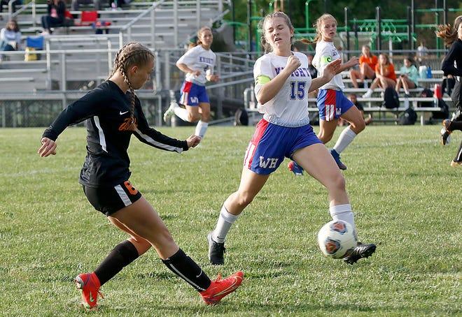 Ashland High School's Chloe Biddinger (6) takes a shot past West Holmes High School's Natalie Rohr (15) during high school girls soccer action Thursday, Sept. 9, 2021 at Ashland Community Soccer Stadium. TOM E. PUSKAR/TIMES-GAZETTE.COM