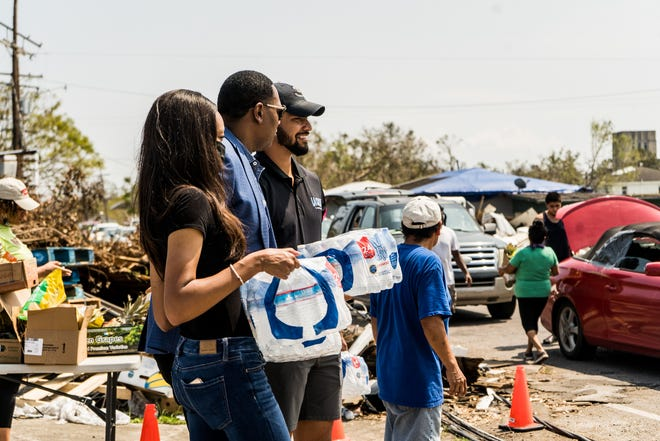 Rapper and businessman Master P (center) helps deliver water to Houma residents Thursday in the wake of Hurricane Ida.