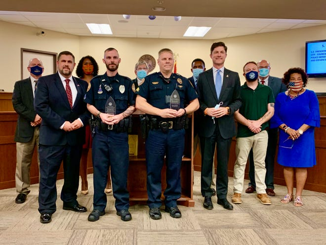 Columbia Police officers Allen Ervin and Steven Schmidt are presented a city commendation award by Mayor Chaz Molder and Columbia City Council for their recent acts of bravery while on duty.