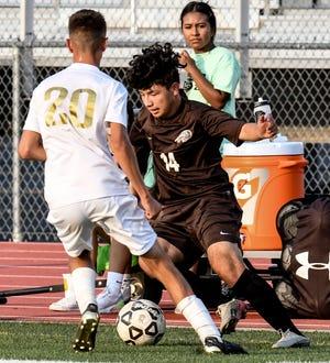 Garden City High School's Juan Viramontes, right, moves the ball past Hays' Karsten Koenke during an Aug. 31 match at Buffalo Stadium.