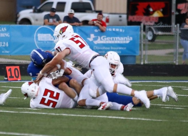Pottsboro's Braden Mullen (52) and Cayson Watson combine on a tackle during the Cardinals' non-district contest against Gunter.