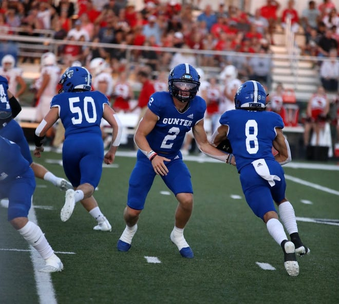 Gunter's Ethan Sloan takes the handoff from Hudson Graham during the Tigers' non-district victory against Pottsboro.