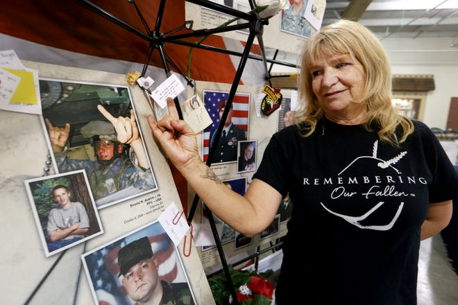 Debbie Austin holds her hand like her son, PFC Shane Austin, at the Remembering Our Fallen from Kansas display in the Pride of Kansas building Friday morning. The traveling pictorial State memorial is displayed in honor of the 20th anniversary of the 9/11 attacks.