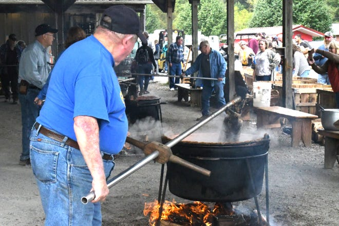 A volunteer helps stir a kettle of apple butter at the 2019 Burlington Apple Harvest Festival. For the second consecutive year, the festival has been cancelled due to COVID concerns.
