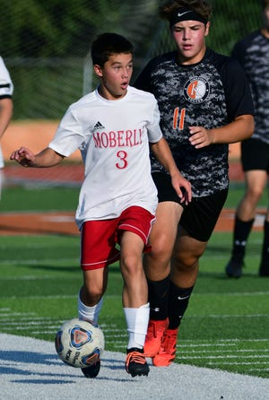 Moberly High School freshman Ryan O'Loughlin looks to distribute the soccer ball as he pushes it upfield Thursday during the Spartans 5-1 victory at North Central Missouri Conference rival Kirksville.