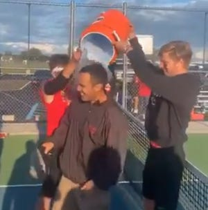 Milan boys tennis coach Nathan Rodriguez gets the water cooler dumped over his head after his team beat Grosse Ile 6-2 Thursday.