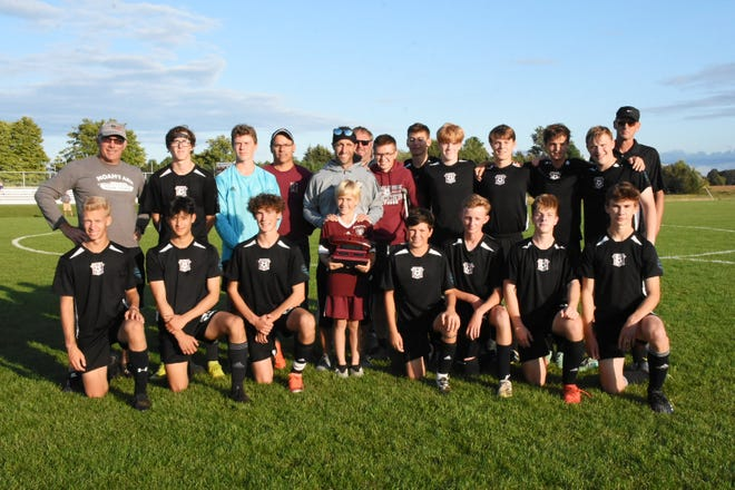 Charlevoix soccer players gather around the Noah's Ark trophy, held by Owen Boss (middle), which is awarded to the winner of the Charlevoix vs. Grayling Noah's Ark game. The game honors the late son, Noah, of former head coach Jon Boss (middle).