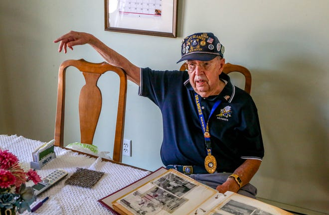 Burt Mollohan, a 90-year-old former Seabee, looks at old photos from his tour at Guantanamo Bay Naval Base in Cuba at his home in West Warwick.