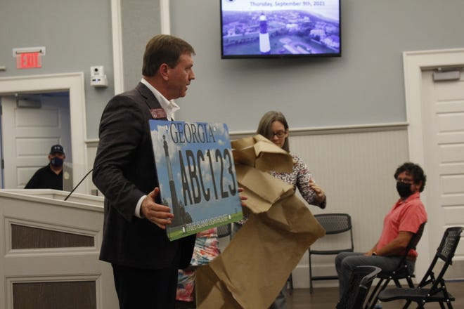 State Representative Jesse Petrea (R-Savannah) holding up the winning design for a GA license plate during the Sept. 9, 2021 Tybee Island city council meeting.