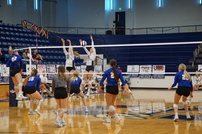 (Left to right in white jerseys) Senior Kenzie Mikish and junior Tieryn Taylor go up for the block against Piedmont in Thursday night's game. Piedmont won in three sets.