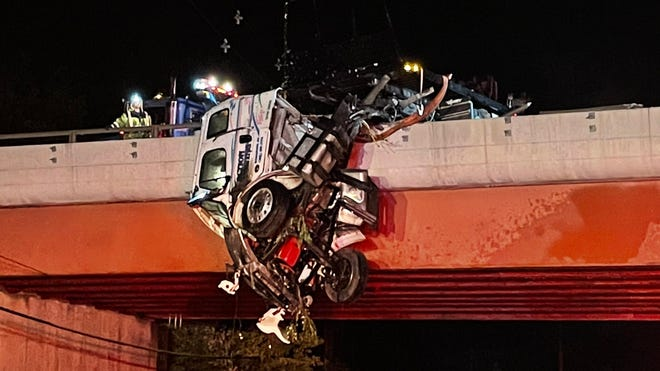 A crane was summoned to lift the rig from the overpass.