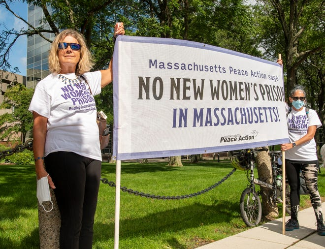 Kris Elinevsky, left, and Quincy Struss hold a banner before marching with others from City Hall to the Worcester County Jail & House of Correction in West Boylston on Friday.