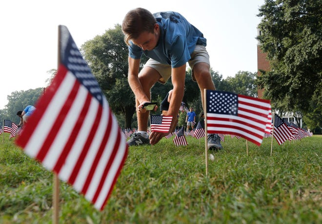 Ethan Lamb uses his cellphone to help drive flags into the ground as University of Alabama students plant flags on the Quad Wednesday, Sept. 11, 2019. Each flag represents a life lost in the 9/11 attacks on the U.S. America in 2001. The University of Alabama Young Americans for Freedom Chapter set out 2,977 flags between the Gorgas Library and Denny Chimes. [Staff Photo/Gary Cosby Jr.]