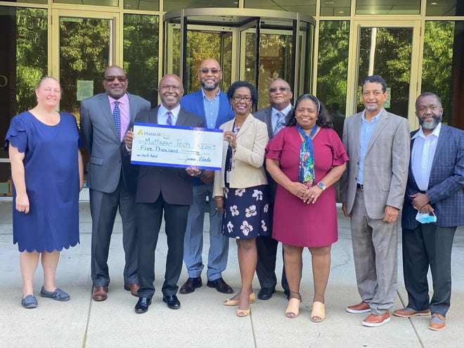 Mattapan founder the Rev. Jacques Dady Jean receives check from HarborOne Bank with Randolph town councilor Ken Clifton and members of Mattapan Tech board of directors.