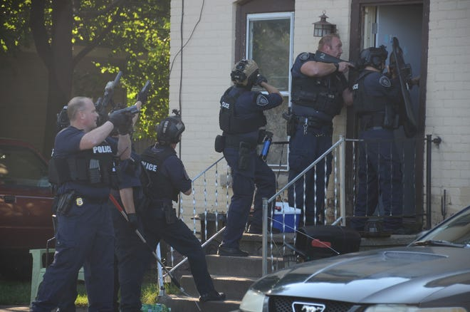 Battle Creek police enter a home Friday with a search warrant looking for evidence of dog fighting.