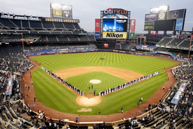 The Miami Marlins and the New York Mets joins members of the New York police and fire departments on the field for pregame ceremonies before a baseball game Tuesday, Sept. 11, 2018, in New York.