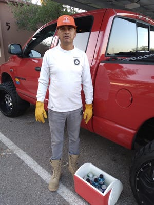 Francisco Rafael Ruíz Soto stands with his ice chest, which he uses to keep drinks on the job.