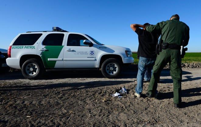 Fotografía de archivo en la que se observa a agentes de la patrulla fronteriza que detienen a un presunto inmigrante ilegal en un costado del Río Grande, cerca de McAllen, Texas (EE.UU.).
