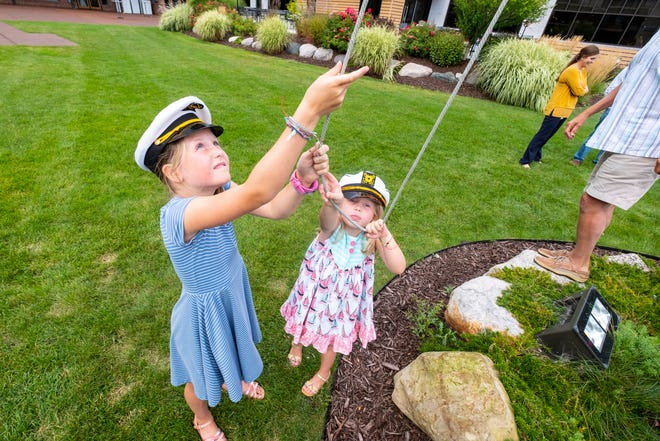 Sydney Mullin, 8, and her sister Avery, 5, work to raise the flags behind the DoubleTree Hotel Thursday, Sept. 9, 2021, in Port Huron. The two sisters have been the official flag officers for the hotel for a couple years.