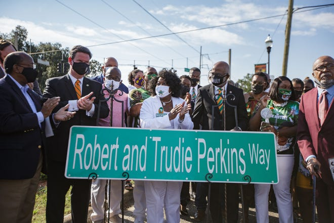 Jackie Perkins, center, is surrounded by family, local elected officials and others as a street sign honoring her parents, Robert and Trudie Perkins is unveiled Friday, Sept. 10, 2021. Gamble Street was renamed Robert and Trudie Perkins Way.