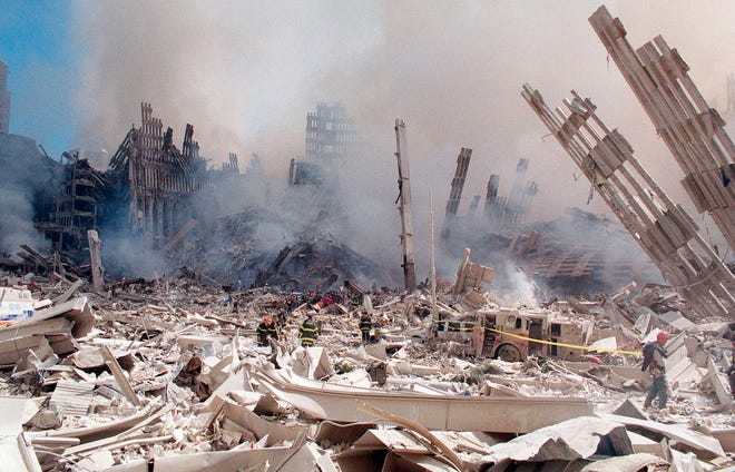 In this Sept. 12, 2001 file photo, firefighters work in the rubble of the World Trade Center towers in New York. Two decades after the twin towers' collapse, people are still coming forward to report illnesses that might be related to the attacks. (AP Photo/Virgil Case, File)