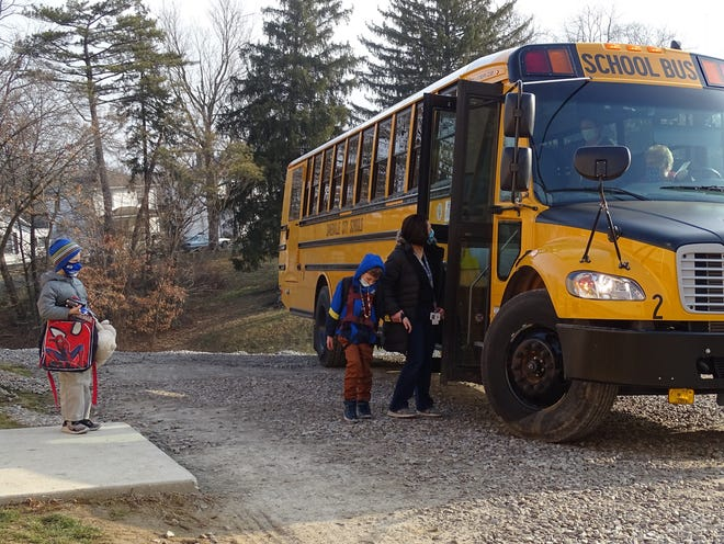 In this file photo from early 2021, John McIntire Elementary students depart from the morning bus. As of September, buses are the only place where the CDC requires masks at school.