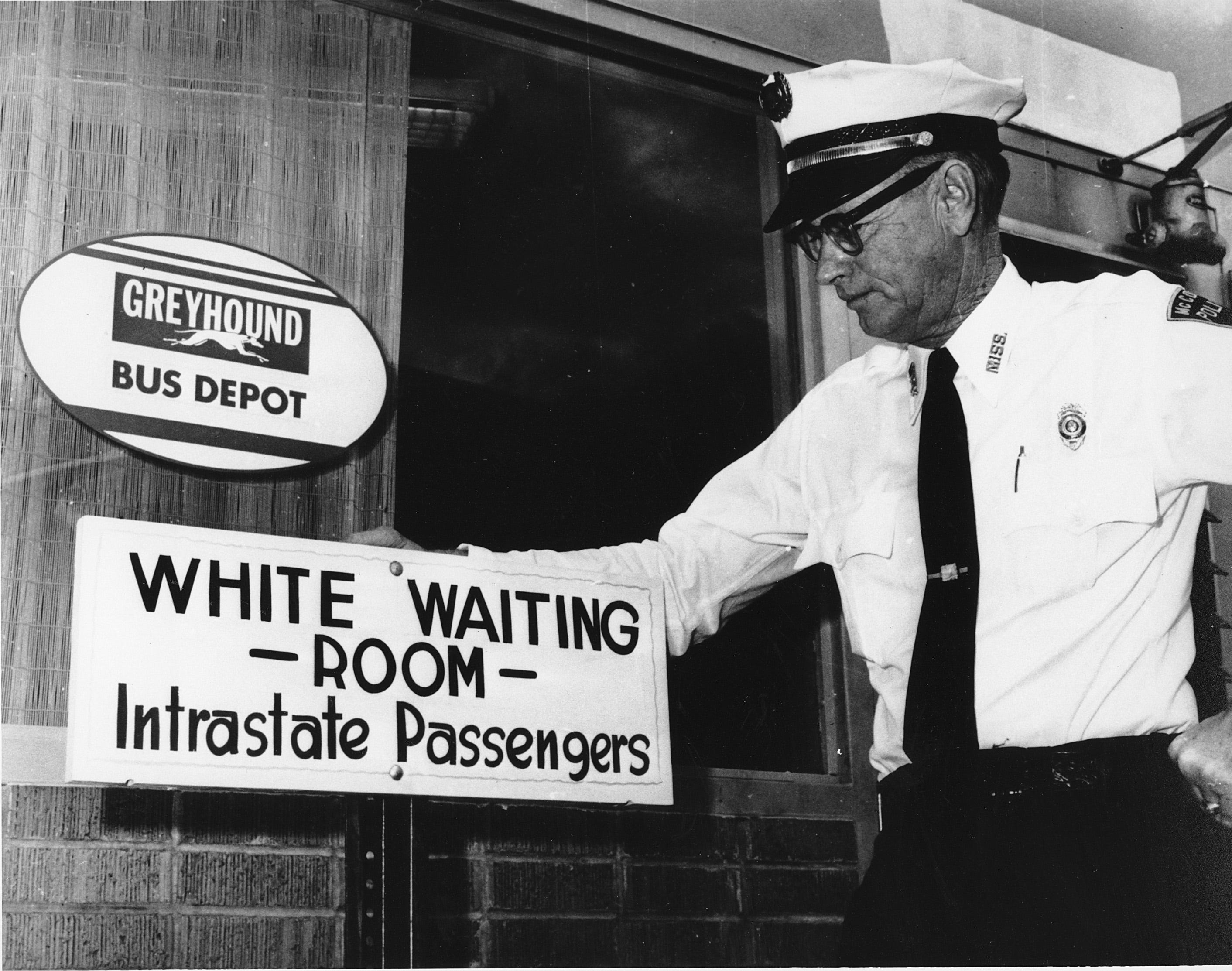 """Police Chief George H. Guy poses beside the """"White waiting room"""" sign posted outside the Greyhound bus terminal in McComb, Miss., on Nov. 2, 1961."""