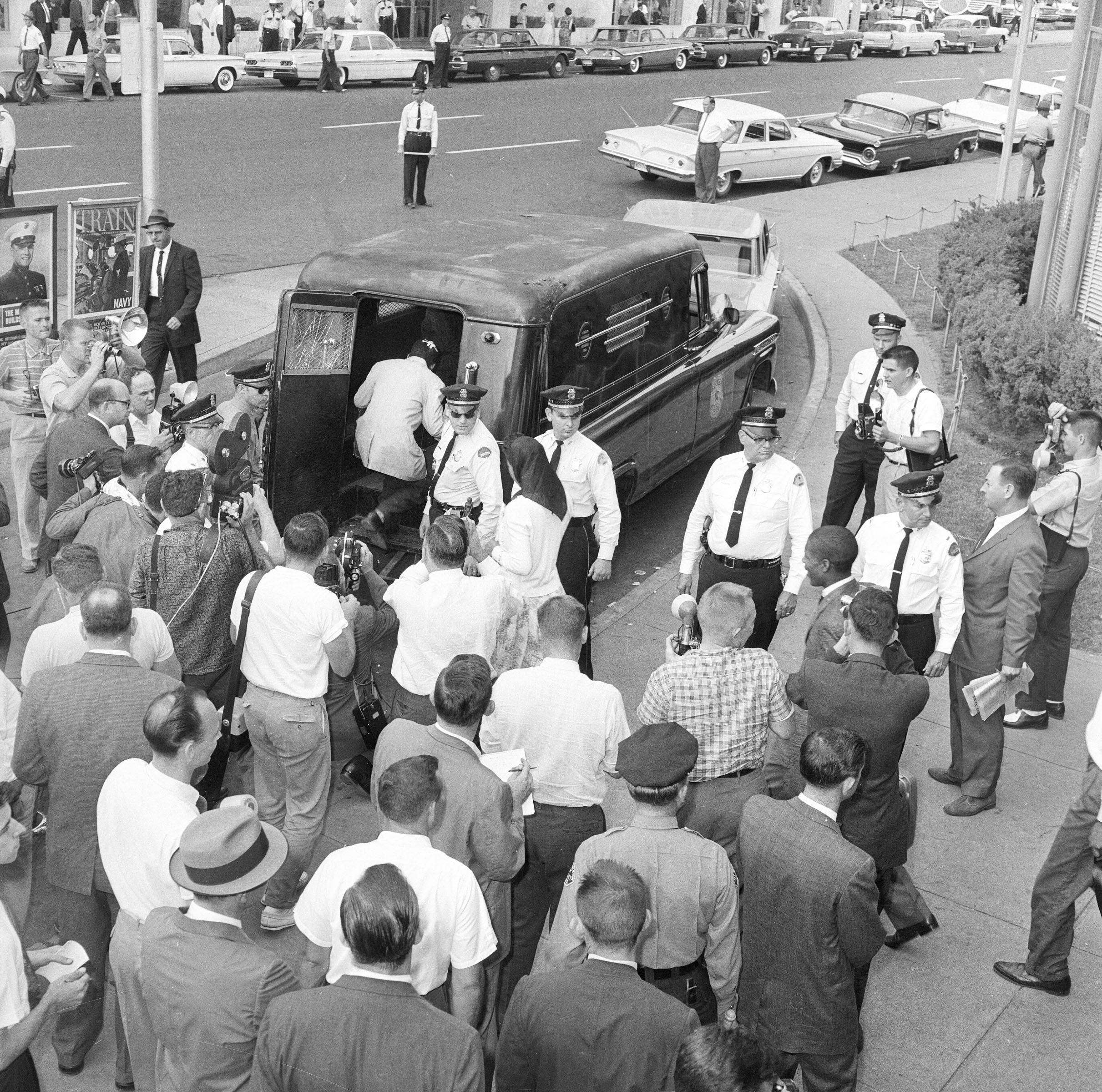"""Fifteen Freedom Riders that arrived on a second bus in Jackson, Miss., are loaded into a paddy wagon at the bus station, May 24, 1961.  They entered the """"whites only"""" waiting room and were arrested for being in violation of state laws."""