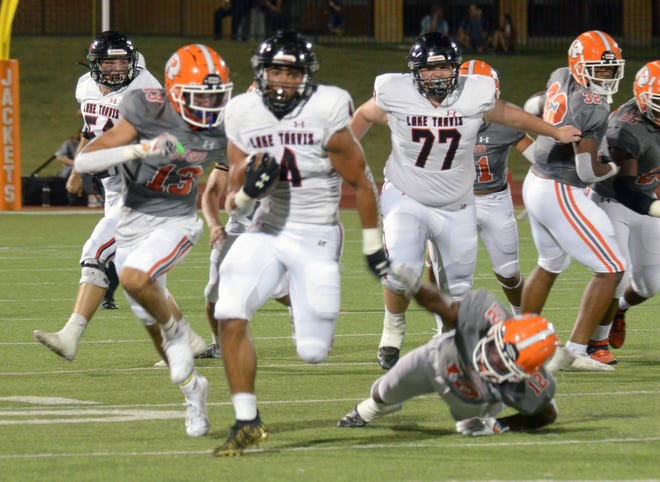 Lake Travis' DJ Johnson leaves a pair of Rockwall defenders behind on his way to a 56-yard touchdown early in the second quarter. Rockwall outscored Lake Travis 59-35 Friday night in Rockwall.