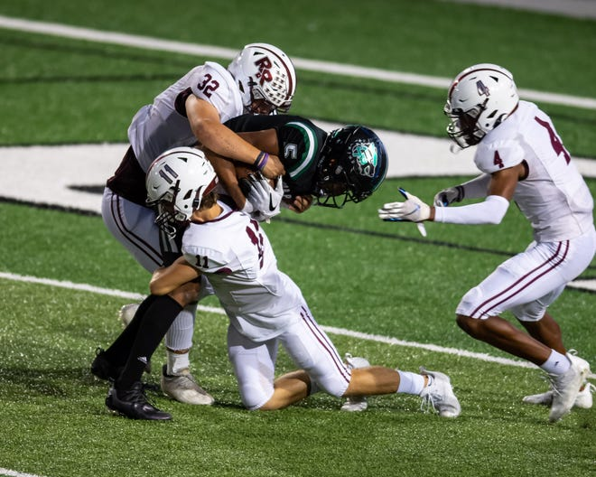 Round Rock defenders, from left, Logan Clifton, Carter Wagner and Jalen Gilbert of Round Rock stop Cedar Park's Nicholas Grullon just short of a touchdown. Round Rock won a nondistrict football game 21-17 over Cedar Park at Gupton Stadium on Sept. 10.