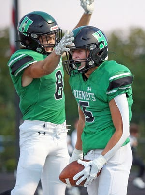 Highland wide receiver Kevin Heichel, right, celebrates with Andrew Ringgenberg after scoring a touchdown during the first half of a football game against the Tallmadge Blue Devils at Highland High School, Tuesday, Sept. 7, 2021, in Medina, Ohio. [Jeff Lange/Beacon Journal]