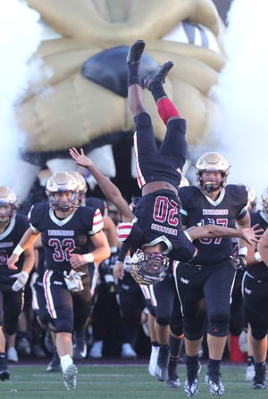 Stow defensive back Taverion Shepherd leads the Bulldogs on to the field with a backflip before the game against Medina on Friday, Sept. 10, 2021 in Stow, Ohio.  [Phil Masturzo/ Beacon Journal]