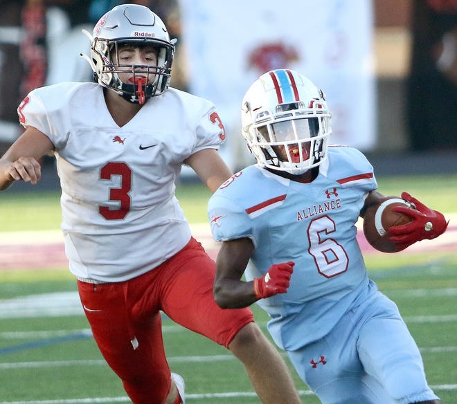 Alliance's Ramhir Hawkins, right, on his way to a long touchdown run with Minerva's Brayden Costea, left, gives chase during first half action Friday, September 10, 2021 at Mount Union Stadium.