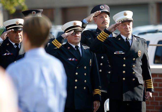 "Ashland Fire Department's Ken Gardnen (left), Dan Raudebaugh and Chief Rick Anderson salute during the singing of ""God Bless America"" at Ashland's 9/11 community remembrance ceremony. TOM E. PUSKAR/TIMES-GAZETTE.COM"