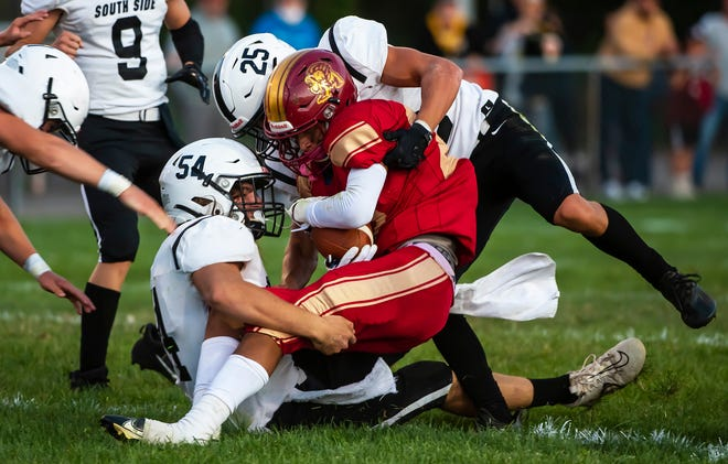 New Brighton's Keandre Williams is brought down by two South Side defenders during their game Friday at New Brighton. [Lucy Schaly/For BCT]