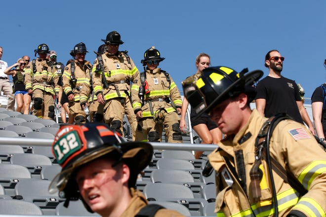 Firefighters from Greater Columbus departments descend the stadium steps Saturday at the Fortress Obetz 9/11 Memorial Stair Climb held to pay tribute to the 343 FDNY firefighters and other first responders who died in the terrorist attacks at the World Trade Center on September 11, 2001. Local firefighters were among the more than 300 participants who climbed the equivalent of the 110 stories of the World Trade Center at the event.