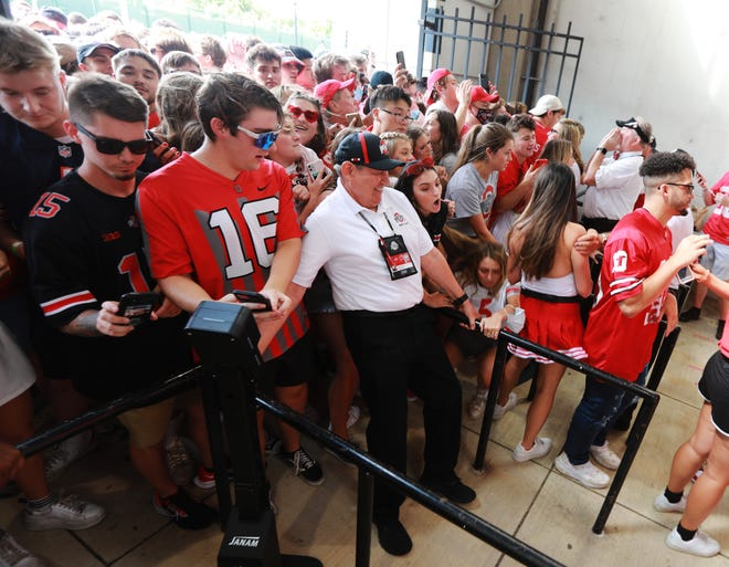 Redcoat Jack Fry tries to keep the crowd back at Ohio Stadium's student section gates as the crowd tries to enter the game. It was the first year using new digital ticket scanners, which caused long lines and delays for fans trying to enter.